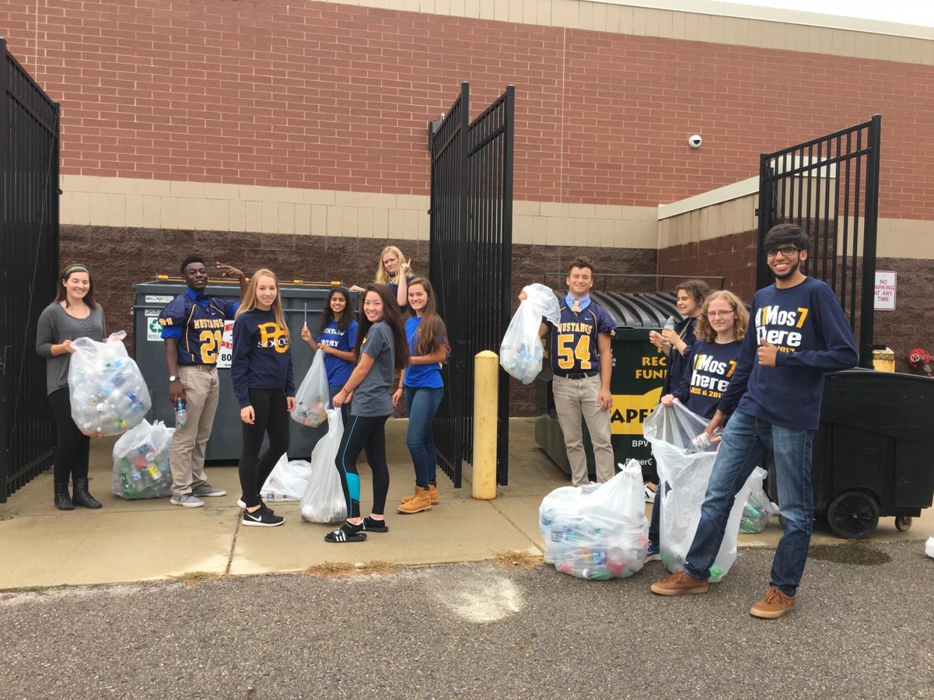 Club members pose for the camera as they throw out the school's recyclables.