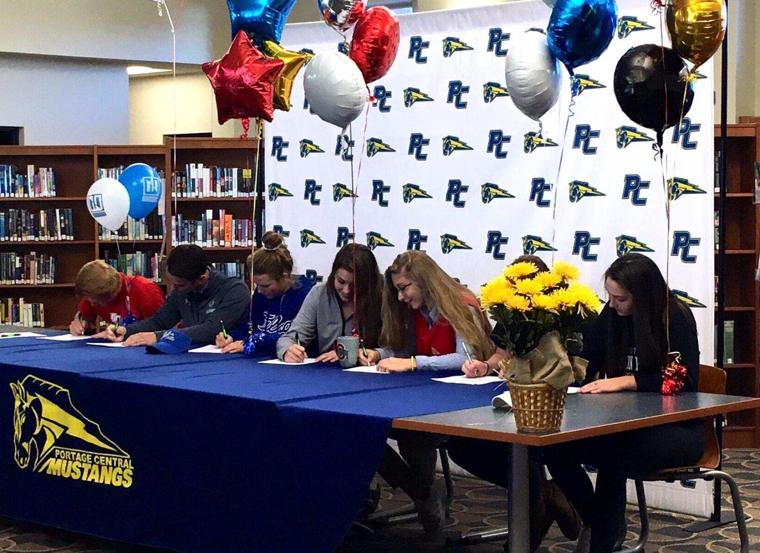 Seniors Carson Hodge, Nick Kolberg, Josie Muffley, Mackenzie Zook, Hannah Corwin, Trinity Cumo, Emma Engle, and Kylee Taylor sign side by side at the table in confirmation to play their sport at each of their respective future schools.