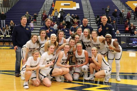The Varsity Girls Basketball Team poses for a photo with their district championship plaque. Coach Rob Brown credits the  team's chemistry and acceptance of roles as players as what  brought them to this championship.